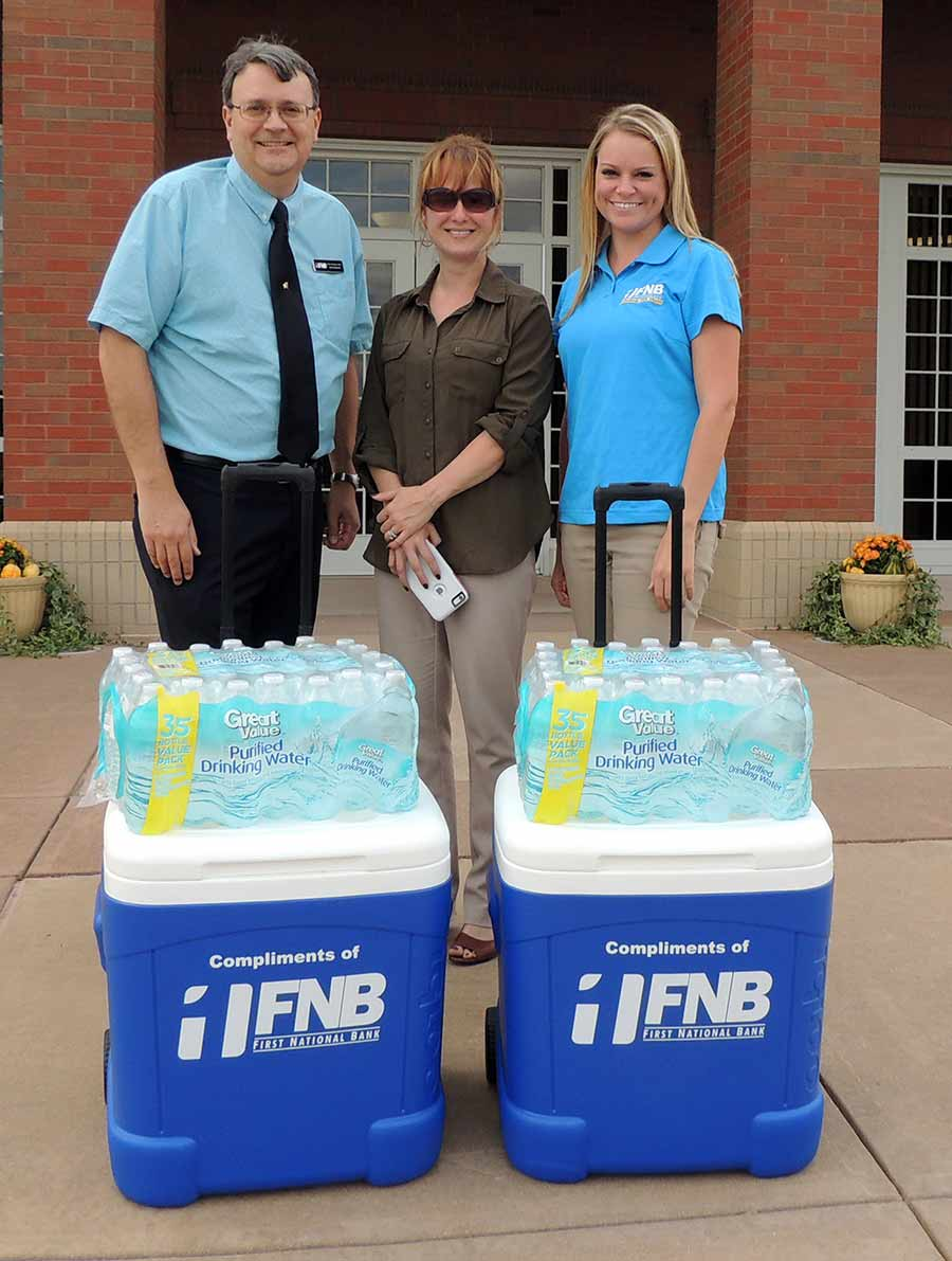 members of First National Bank standing next to coolers and water bottles