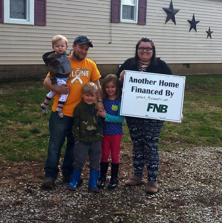 family posing in front of new home