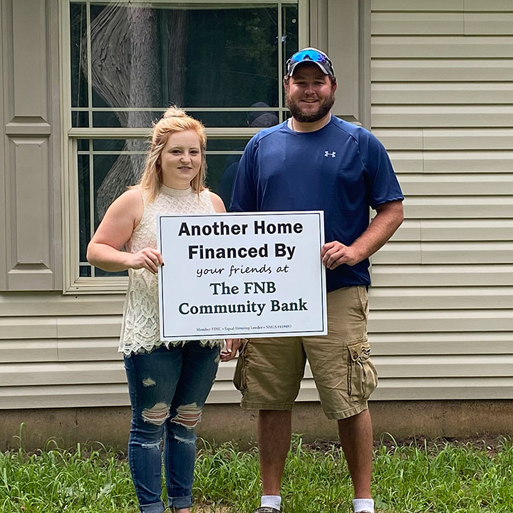 young couple posing in front of their new home