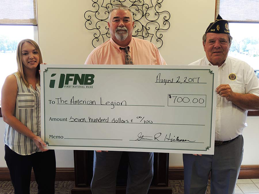 First National Bank employees holding a donation check for the Patoka American Legion